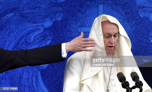 A priest attends the Pope as a gust of wind catches Pope Francis' cassock as he visits the holy shrine on August 26 2018 in Knock Ireland Pope...