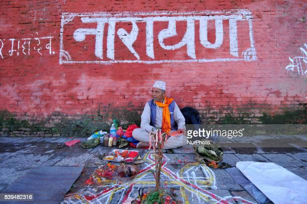 A Priest awaits devotees to offer ritual prayer at the Bank of Bagmati River of Pashupatinath Temple during Rishi Panchami Festival celebrations at...