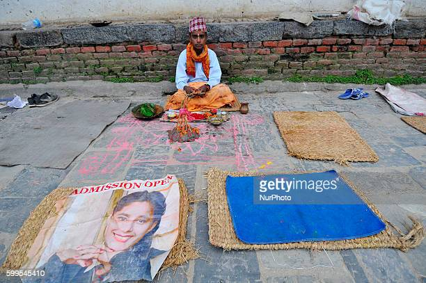 A Priest awaits for the devotees to offering ritual prayer at the Bank of Bagmati River of Pashupatinath Temple during Rishi Panchami Festival...