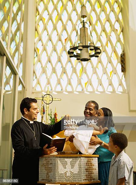 priest baptizing a baby girl - baptism stock pictures, royalty-free photos & images
