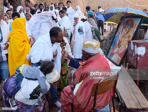 A priest blesses a man at Beta Mariam Church on January 7 2016 in Lalibela Ethiopia Thousands of adhearants to the Ethiopian Orthodox Faith descend...