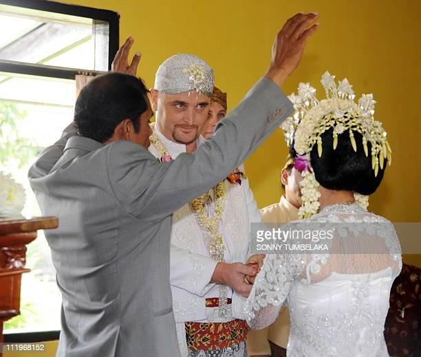 A priest blesses Australian groom Martin Eric Stephens and his bride Winarni Puspayanti alias Christine during their wedding ceremony at Kerobokan...
