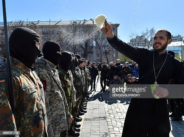 A priest blesses fighters of the Ukrainian Donbass volunteer battalion on March 17 2015 during a farewell ceremony in the center of Kiev before their...