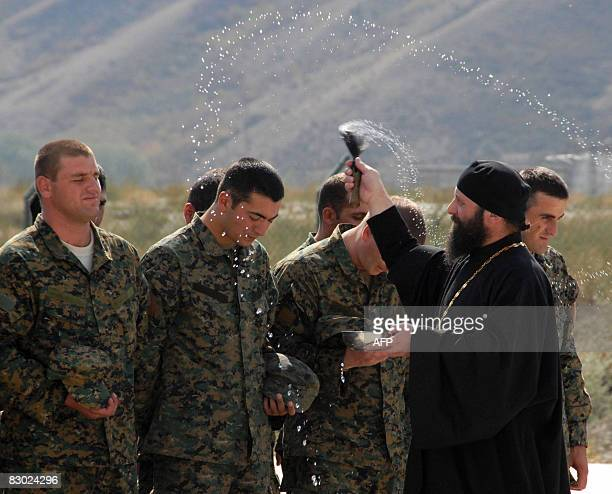 A priest blesses Georgian soldiers at their base in Gori on September 26 2008 Georgia's parliament on Friday approved a draft law that will...