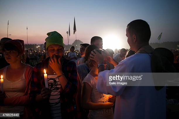 A Priest blesses teenangers during the Youth Meeting Lednica 2000 on June 6 2015 in Pola Lednickie Poland Lednica 2000 is an annual gathering of...