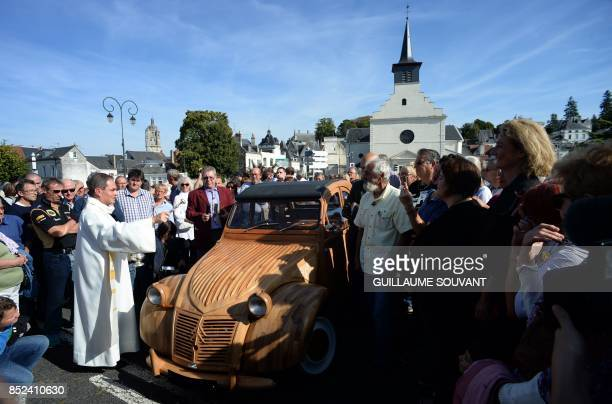 A priest blesses the wooden 2CV Citroen car made by French cabinetmaker Michel Robillard in the streets of Loches Central France on September 23 2017...