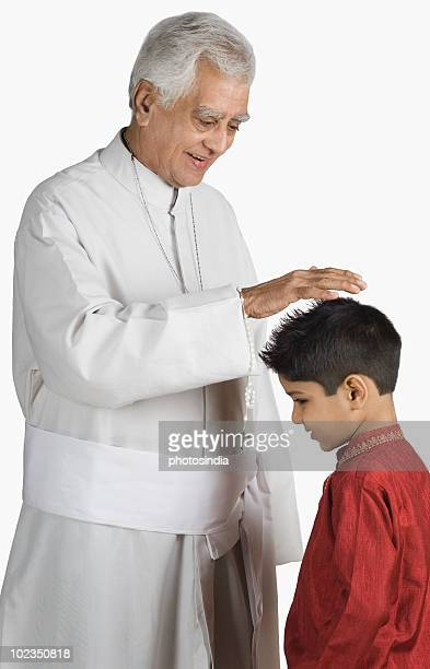 Priest blessing a boy and smiling