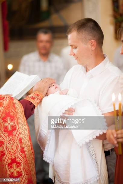 Priest blessing baby boy in church