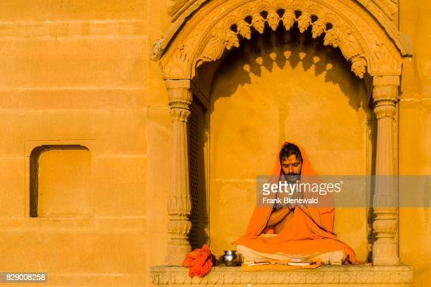 A priest Brahmin is sitting and praying on a balcony at the holy river Ganges at Lalita Ghat in the suburb Godowlia