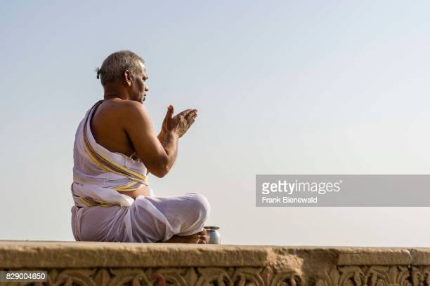 A priest Brahmin is sitting and praying on a platform at the holy river Ganges at Dashashwamedh Ghat Main Ghat in the suburb Godowlia