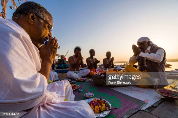 A priest Brahmin is working with pilgrims at the holy river Ganges at Dashashwamedh Ghat Main Ghat in the suburb Godowlia