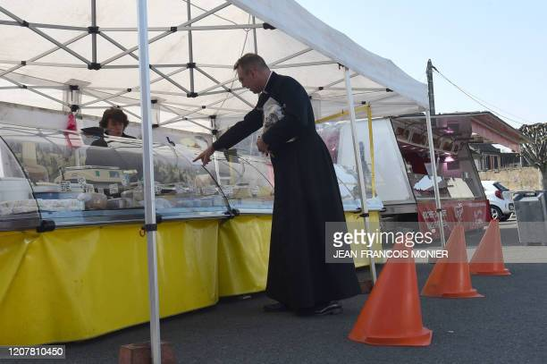 Priest buys cheese from behind red cones placed to define a space of one meter between each customer, during the weekly market, on March 20 in...