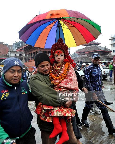 A priest carries Nepalese living goddess Kumari Mateena Shakya towards The Taleju Temple in Kathmandu on January 9 on the occassion of the Changu...