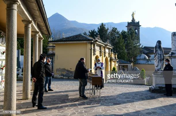 TOPSHOT A priest celebrates funeral service without relatives inside the cemetery of Zogno near Bergamo northern Italy on March 21 2020 Italy on...