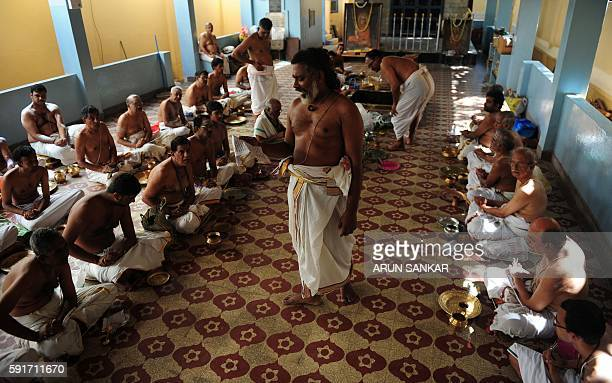 A priest chants manthras as members of the Hindu Brahmin community perform an annual ritual on occasion of Avani Avittam in Chennai on August 182016...