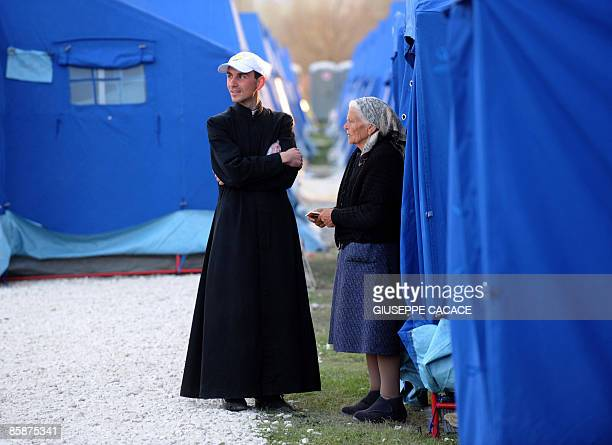 A priest chats with an elderly woman in a camp for evacuated people in Paganica on April 9 2009 Italians prepared today to lay to rest the nearly 300...