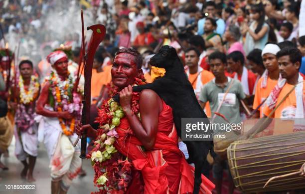A priest dances while carrying a sacrificial goat during the Deodhani Festival at the Kamakhya Temple on August 18 2018 in Guwahati India The...