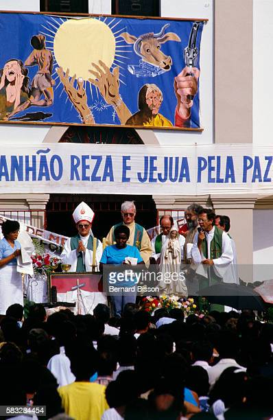 Priest Davi Alves da Silva preaches from a raised platform outside a church to a crowd of followers of Liberation Theology The promotion of direct...