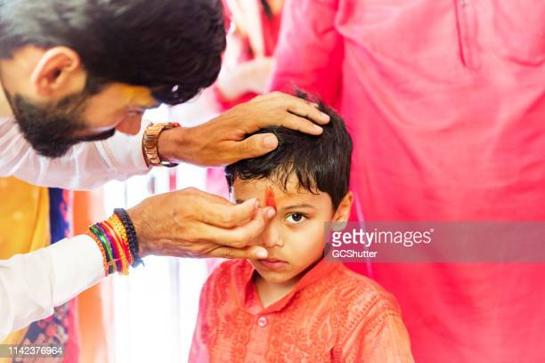 """priest doing """"tilak"""" on the forehead of a child as a part of hindu prayers - hinduism stock pictures, royalty-free photos & images"""