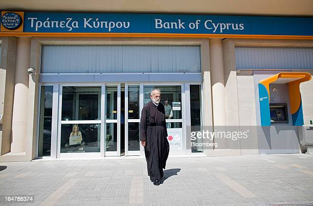 A priest exits after visiting a Bank of Cyprus Plc branch after it opened for the first time in two weeks in Nicosia Cyprus on Thursday March 28 2013...