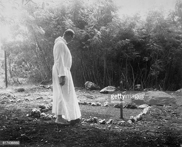A priest Father Sylvan Conover Order Friars Minor prays at a grave site thought to be that of famed aviator Amelia Earhart and her navigator Fred...