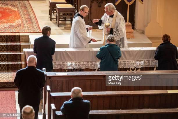 """Priest Gerald Goesche gives a communion to the members of the Catholic group """"Freundeskreis St. Philipp Neri"""" at Saint Afra church despite the..."""