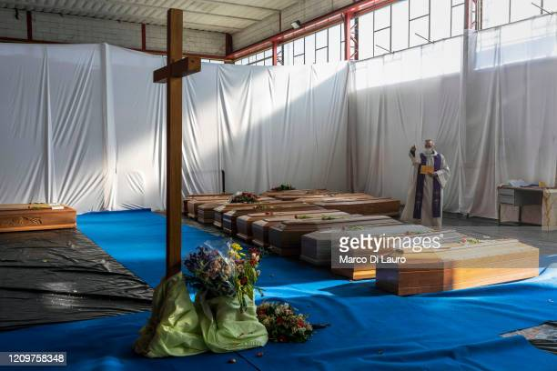 Priest gives a blessing in the hangar where 18 coffins of victims of COVID-19 wait to be transported to Florence by the Italian Army to be cremated...