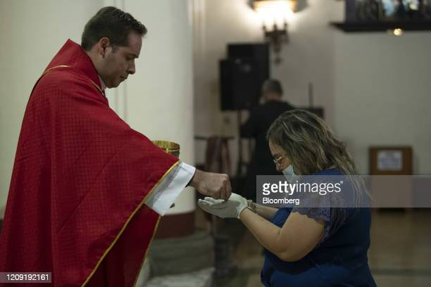 A priest gives communion to a person wearing a protective mask and gloves during a Palm Sunday mass in Caracas Venezuela on Sunday April 5 2020 Amid...