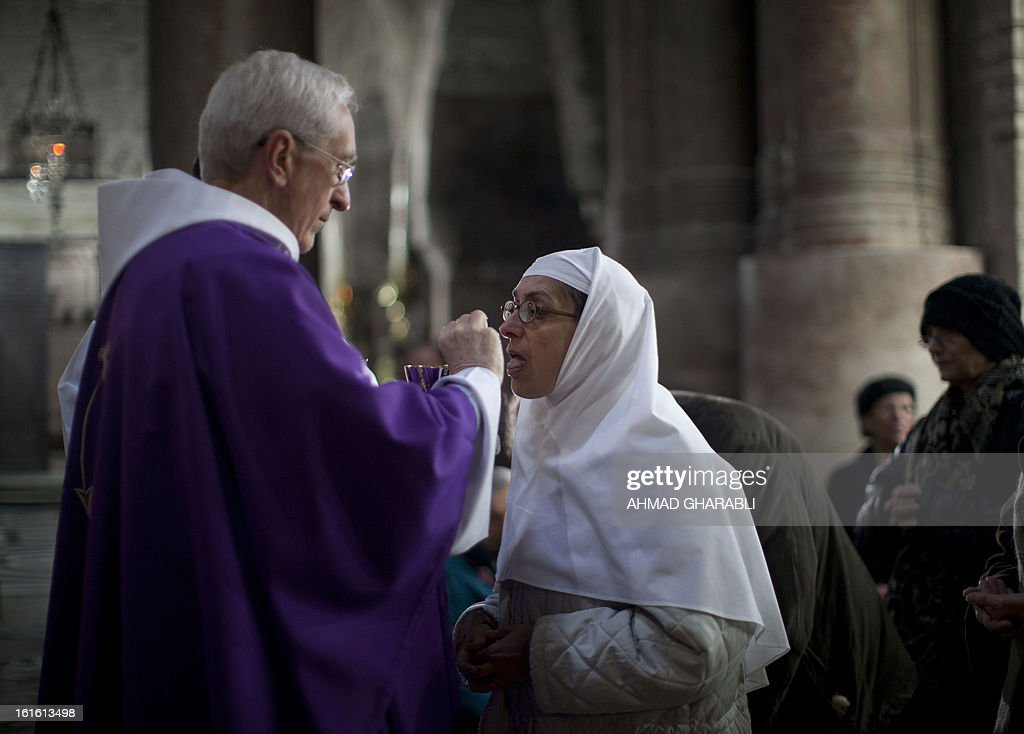 A priest gives holy communion to a nun during mass at a church Holy Sepulcher in Jerusalem's Old City to mark Ash Wednesday, which launches the traditional period of penitence ahead of Easter in the Christian calendar, on February 13, 2013. The Catholic Church faced a tricky transition on Tuesday as it prepared to elect a new pope, with many faithful still reeling from the shock resignation of Pope Benedict XVI.