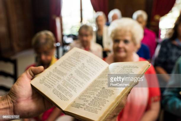 priest holding a book of psalms addressing the congregation - preacher stock pictures, royalty-free photos & images