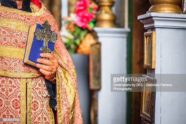 Priest holding a cross and bible
