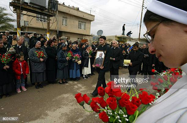 A priest holding a framed picture of Archbishop Paulos Faraj Rahho walks amid mourners during his funeral in the northern Iraqi Christian village of...