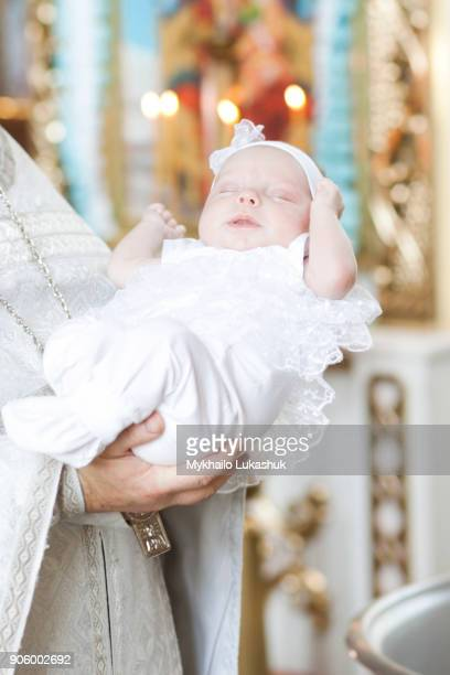 priest holding baby girl in church - baptism stock pictures, royalty-free photos & images