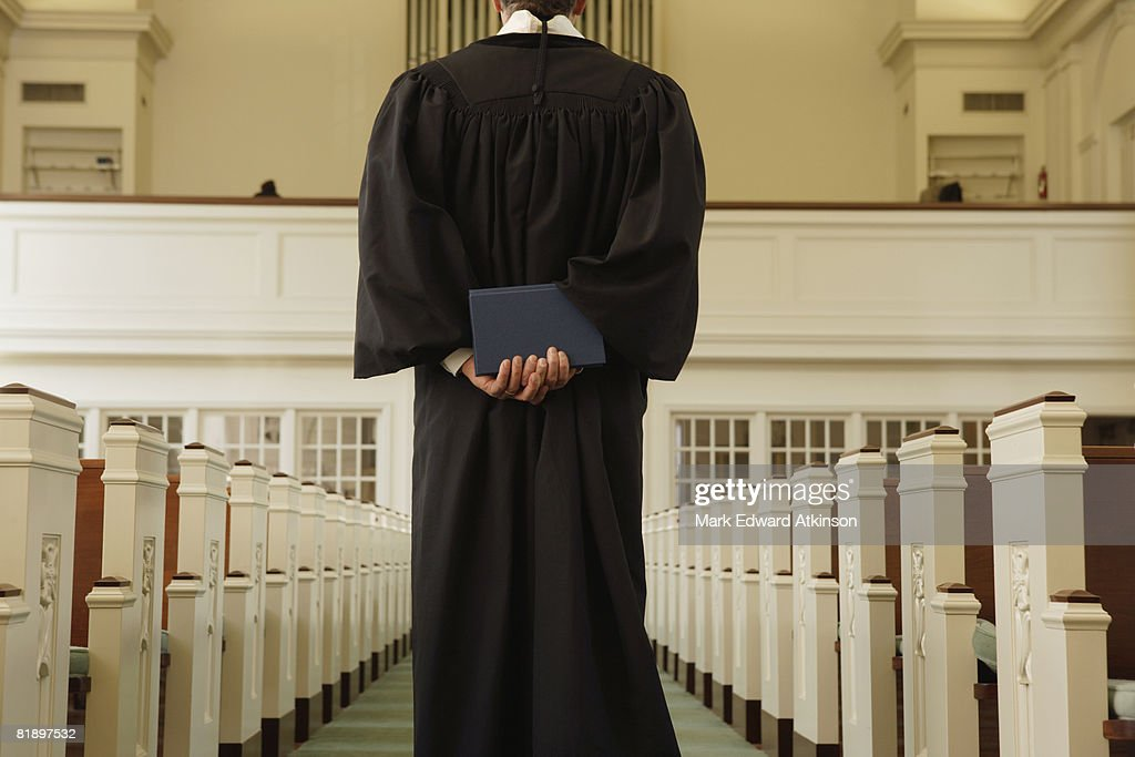 Priest holding bible behind back : Stock Photo