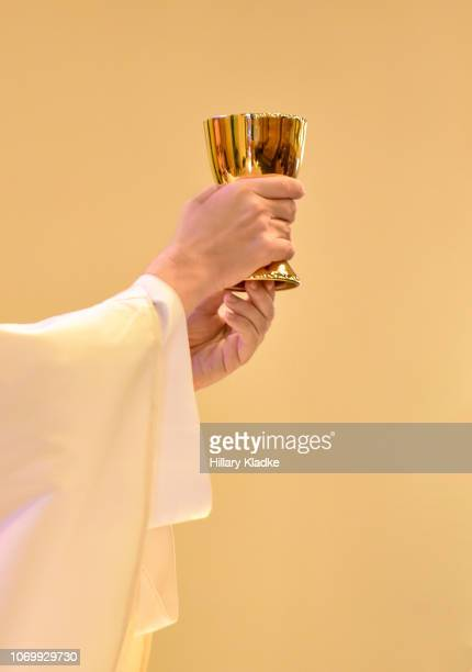priest holding golden cup - religious mass stock pictures, royalty-free photos & images