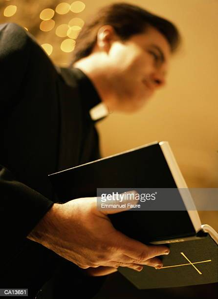 Priest holding open bible, close-up, low angle view