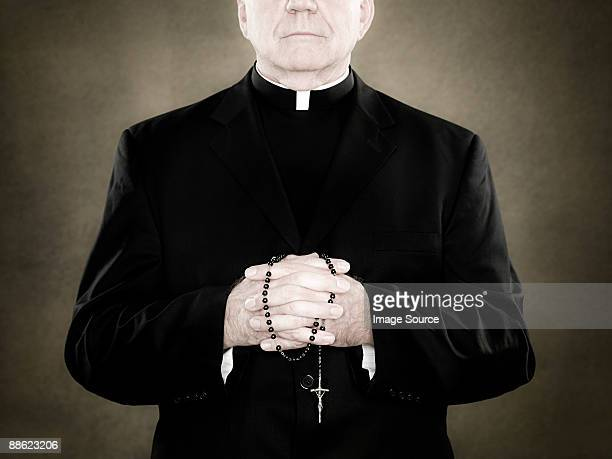 a priest holding prayer beads - katholicisme stockfoto's en -beelden