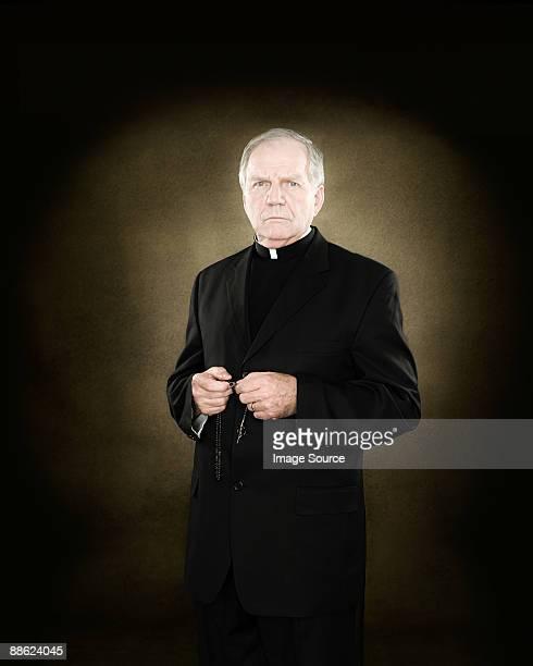 a priest holding prayer beads - sacerdote fotografías e imágenes de stock