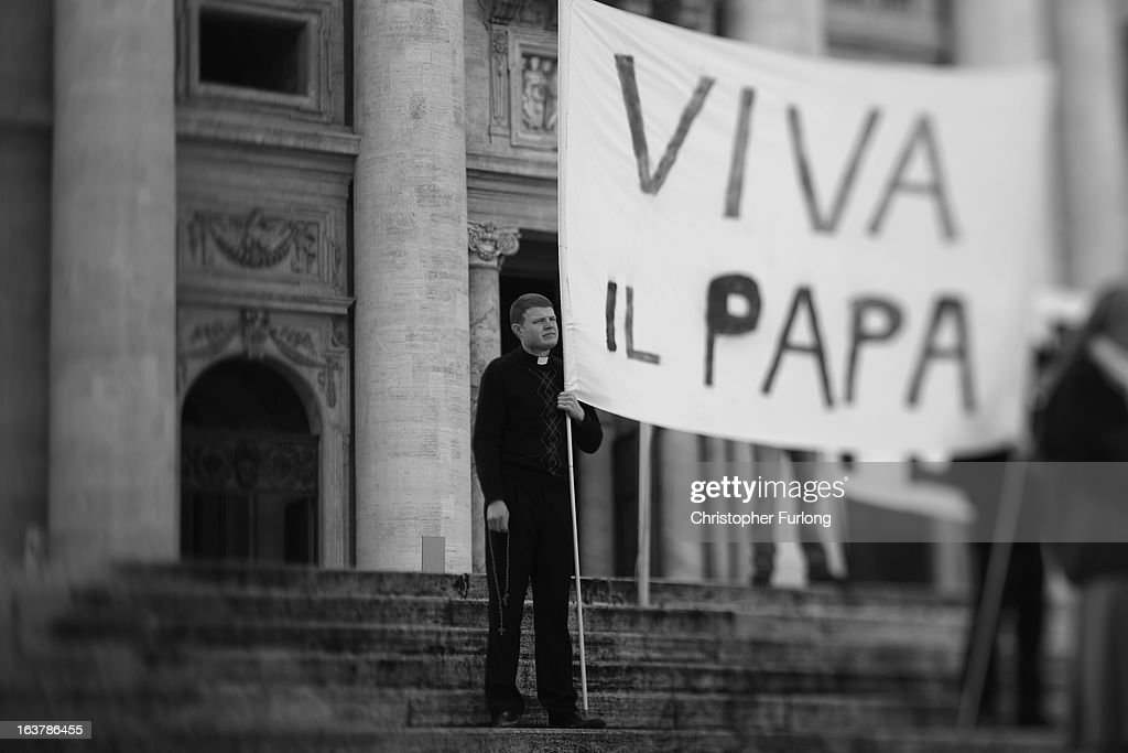 . A priest holds a banner in front of St Peter's Basilica as he takes part in a prayer meeting for Pope Francis on March 15, 2013 in Vatican City, Vatican. Daily life continues around the vatican as romans prepare for the inauguration mass of Pope Francis, the first ever Latin American Pontiff.