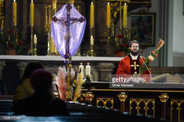 A priest holds a palm as he delivers the Palm Sunday mass to parishioners inside Podgorze Church during the declared state of pandemic by the...