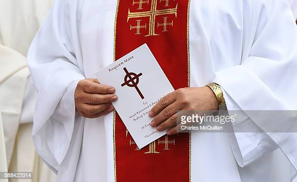 A priest holds an order of service for the funeral of the late retired Bishop of Derry Dr Edward Daly as he lies in state at St Eugene's Cathedral on...
