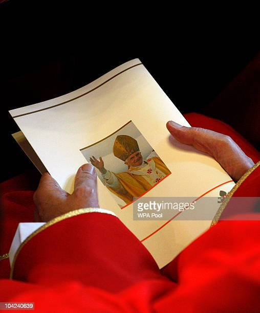 A priest holds an order of service whilst Pope Benedict XVI conducts a mass at Westminster Cathedral during the third day of his State Visit on...