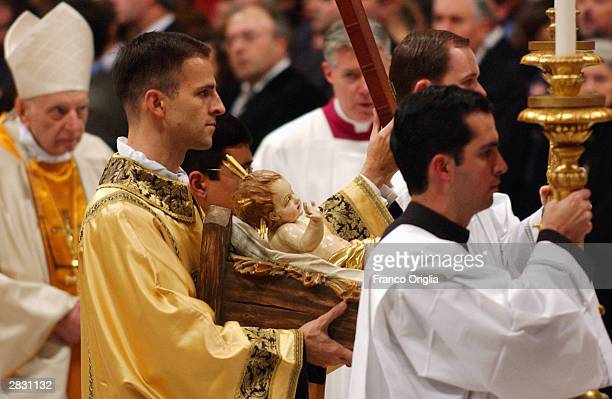 A priest holds the crib in procession during the midnight mass celebrating the birth of Christ at St Peter's Basilica December 25 2003 in Vatican...