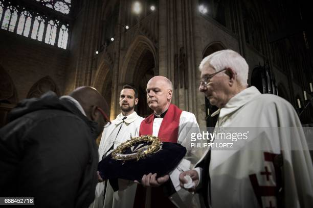 A priest holds the Crown of Thorns as the relic of the passion of Christ is presented to faithfuls at the NotreDame Cathedral in Paris on April 14...
