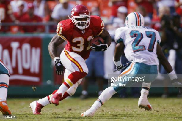 Priest Holmes of the Kansas City Chiefs goes up against safety Arturo Freeman of the Miami Dolphins in the fourth quarter on September 29 2002 at...
