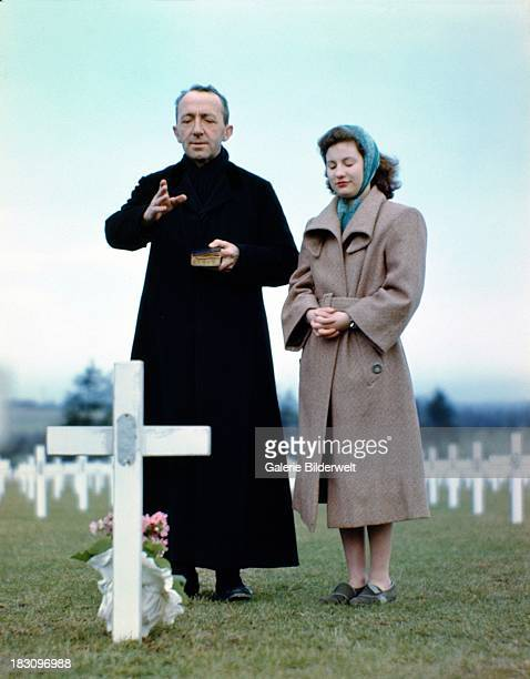A priest in black holding a bible and young woman in prayer standing at a grave decorated with flowers in one of the new cemeteries for soldiers...