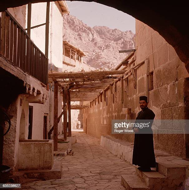 A priest in black robe and hat stands in a stonepaved passageway at St Catherine's Monastery founded in the Sinai desert by order of the Roman...