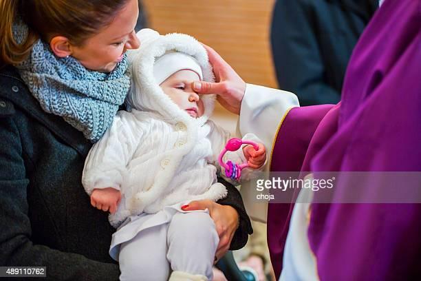 Prêtre est baptizing petit bébé fille dans une église