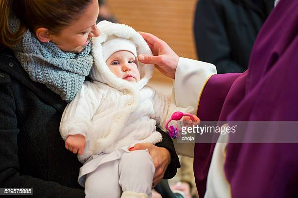 Priest is baptizing little baby girl in a church