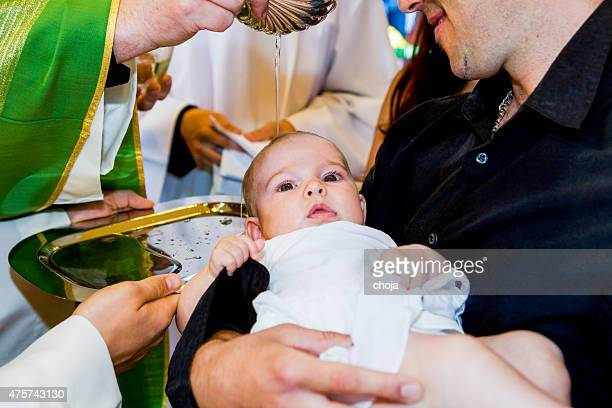 priest is baptizing little baby in a church. - baptism stock pictures, royalty-free photos & images